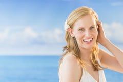 Blonde Frau gegen Meer am Strand Stockbilder