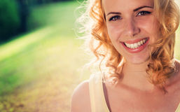 Blonde Frau, gelocktes Haar in der grünen Natur Sonniger Sommer Lizenzfreie Stockfotos