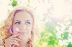 Blonde Frau, gelocktes Haar in der grünen Natur Sonniger Sommer Lizenzfreie Stockfotografie