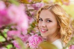 Blonde Frau, gelocktes Haar gegen rosa Baum im blossoom Lizenzfreies Stockbild