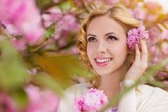 Blonde Frau, gelocktes Haar gegen rosa Baum im blossoom Stockbild