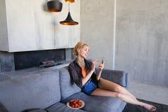 Blonde Frau hält Handy und isst die reife Erdbeere und sitzt Stockfotografie