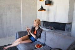Blonde Frau hält Handy und isst die reife Erdbeere und sitzt Stockbild