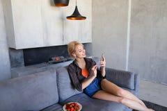 Blonde Frau hält Handy und isst die reife Erdbeere und sitzt Lizenzfreie Stockfotos