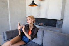 Blonde Frau hält Handy und isst die reife Erdbeere und sitzt Lizenzfreies Stockbild