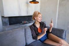 Blonde Frau hält Handy und isst die reife Erdbeere und sitzt Lizenzfreie Stockbilder