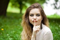 Blonde Frau hat Zeigefinger zu den Lippen als Zeichen der Ruhe gesetzt Lizenzfreie Stockbilder
