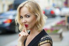 Blonde Frau hat Zeigefinger zu den Lippen als Zeichen der Ruhe gesetzt Stockfotos