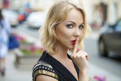 Blonde Frau hat Zeigefinger zu den Lippen als Zeichen der Ruhe gesetzt Stockfotografie