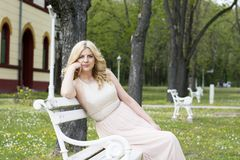 Blonde Frau im Abendkleid, das auf weißer Bank sitzt Lizenzfreies Stockbild