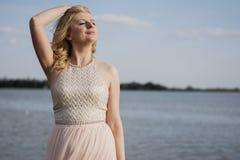 Blonde Frau im Abendkleid am See Lizenzfreie Stockfotos