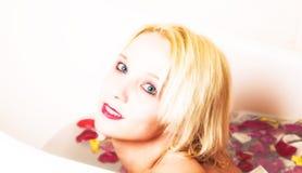 Blonde Frau im Bad des rosafarbenen Blumenblattes Stockfoto