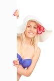 Blonde Frau im Badeanzug, der ein Panel anhält Stockbild