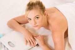 Blonde Frau im Badekurort, der ein Gewichtskalen anhält Lizenzfreies Stockbild