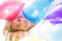 Blonde Frau im Bett mit bunten Ballonen Lizenzfreie Stockfotos