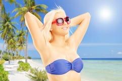 Blonde Frau im Bikini, der auf einem tropischen Strand sich entspannt Lizenzfreies Stockfoto