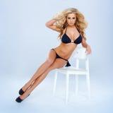 Blonde Frau im Bikini, der auf Stuhl sitzt Stockbild
