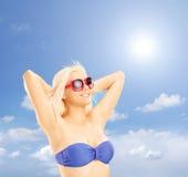 Blonde Frau im Bikini, der gegen einen blauen Himmel sich entspannt Stockbild