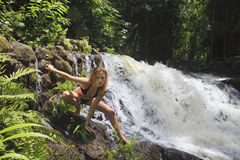 Blonde Frau im Bikini durch Wasserfall Lizenzfreies Stockfoto