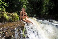 Blonde Frau im Bikini durch Wasserfall Lizenzfreie Stockfotografie