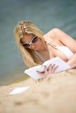 Blonde Frau im Bikini entspannen sich auf Strand mit Buch Lizenzfreie Stockfotos