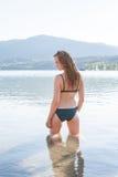 Blonde Frau im Bikini kniend im seichten Wasser Stockbilder