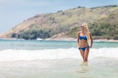 Blonde Frau im blauen Bikini auf weißem tropischem Strand Stockbilder