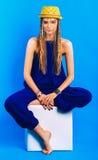 Blonde Frau im blauen Gesamten und im Hut, die auf Stuhl sitzt Stockfoto
