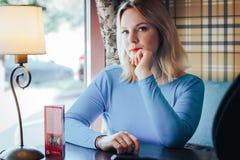 Blonde Frau im blauen Kleid im Café Lizenzfreie Stockfotos