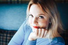 Blonde Frau im blauen Kleid im Café Stockbild