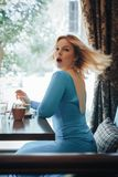 Blonde Frau im blauen Kleid im Café Stockfotos