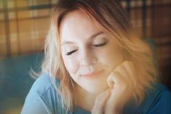 Blonde Frau im blauen Kleid im Café Stockfoto