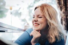 Blonde Frau im blauen Kleid im Café Lizenzfreies Stockbild