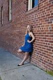 Blonde Frau im blauen Kleid, das auf Backsteinmauer sich lehnt Lizenzfreies Stockfoto