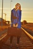Blonde Frau im blauen Mantel, der auf railraod aufwirft Lizenzfreies Stockbild