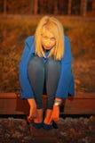 Blonde Frau im blauen Mantel, der auf railraod aufwirft Stockfotos