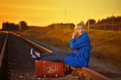 Blonde Frau im blauen Mantel, der auf railraod aufwirft Lizenzfreie Stockbilder