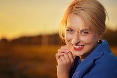 Blonde Frau im blauen Mantelporträt Stockfotografie