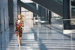 Blonde Frau im bunten Kleid, das das c durchläuft Stockfoto