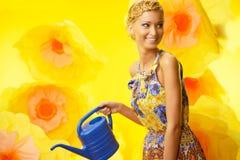 Blonde Frau im bunten Kleid unter Blumen Lizenzfreies Stockfoto