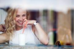 Blonde Frau im Café, das in camera flirtet und schaut Lizenzfreie Stockfotos