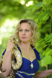 Blonde Frau im eleganten Kleid mit einer Pythonschlange Stockfoto
