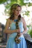 Blonde Frau im eleganten Kleid mit einer Pythonschlange Stockfotografie