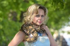 Blonde Frau im eleganten Kleid mit einer Pythonschlange Stockbilder