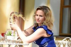 Blonde Frau im eleganten Kleid mit einer Pythonschlange Lizenzfreies Stockfoto