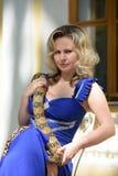 Blonde Frau im eleganten Kleid mit einer Pythonschlange Stockbild