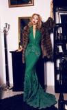 Blonde Frau im eleganten Kleid und im Pelzmantel, die im luxuriösen Innenraum aufwirft Lizenzfreie Stockbilder