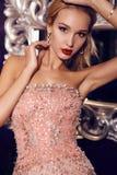 Blonde Frau im eleganten Pailletten-Kleid, das im luxuriösen Innenraum aufwirft Stockbild