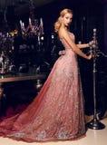 Blonde Frau im eleganten Pailletten-Kleid, das im luxuriösen Innenraum aufwirft Lizenzfreies Stockbild