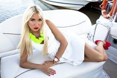 Blonde Frau im eleganten weißen Kleid auf Boot Sommerferien auf Segelboot lizenzfreies stockfoto